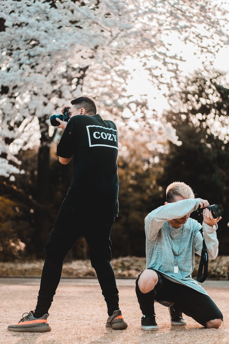 two photographers taking pictures with cameras